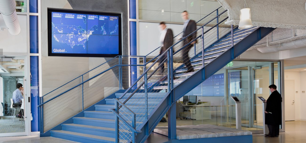 Motion shot of two men descending a staircase in an open-layout office