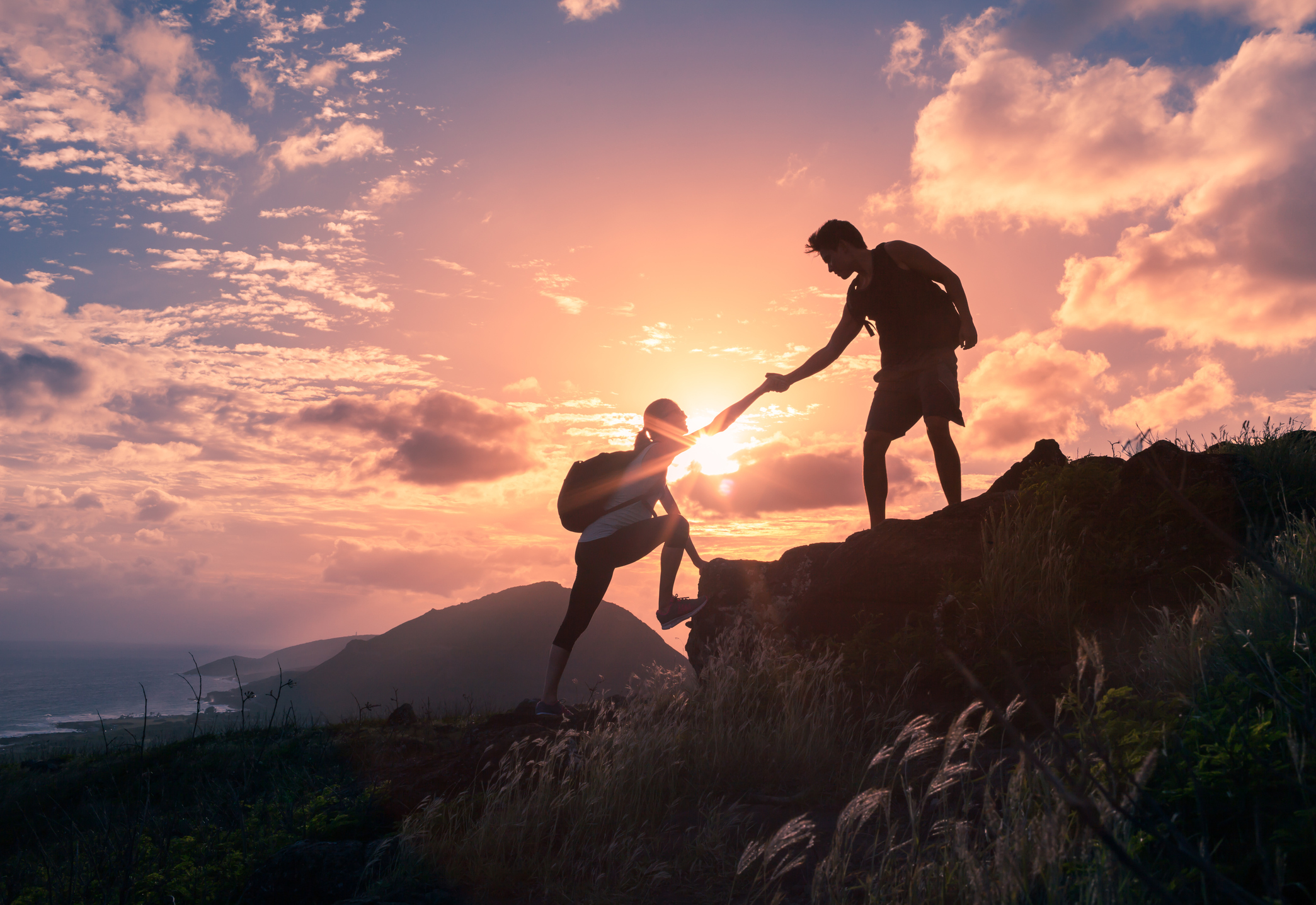 two hikers helping each other