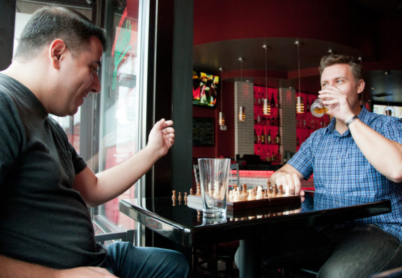 Dave Romero (left) and Alex Fedorov (right) play chess and enjoy a few beers.