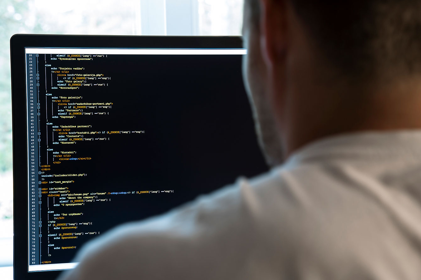 Man coding in front of computer screen