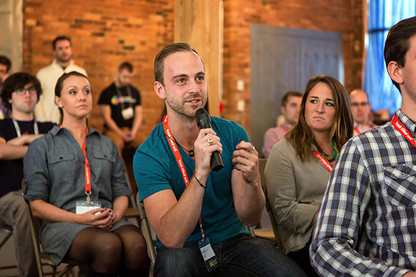 An audience member asks a question during a panel discussion on the main stage.