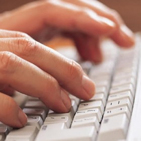 A pair of hands typing on a keyboard