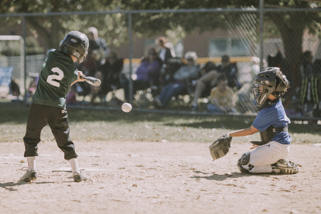 A little league baseball player swings and misses