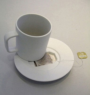 A mug with a plate that has a hole in it for a tea bag when you're done with it