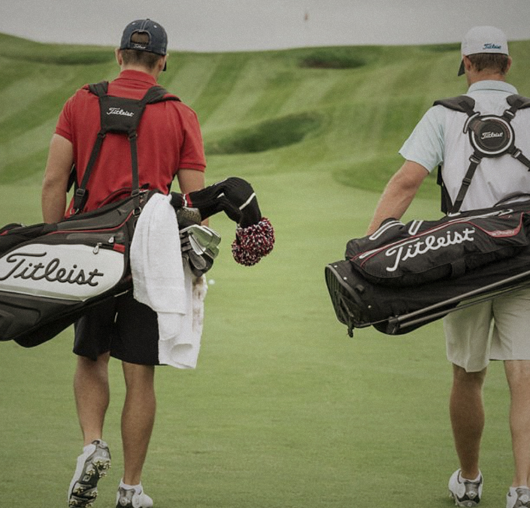 Golfers carrying Titleist golf bags