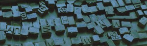 A stylized image of metal typographic characters lying in a jumble in their wooden case.